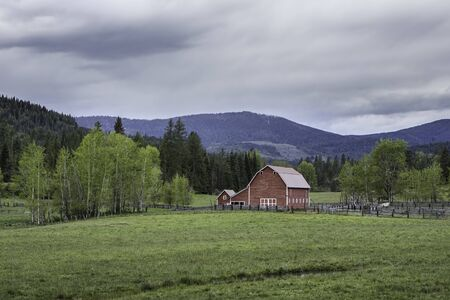 An old red barn in a green pasture in north Idaho.