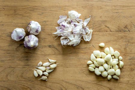 An overview of Garlic bulbs, cloves, and peels on a wooden cutting board. Stok Fotoğraf