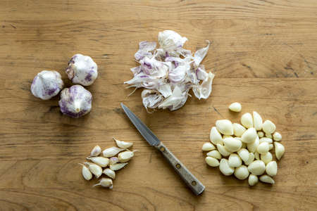 An overview of garlic bulbs, cloves, and peels  and a knife on a wooden cutting board.