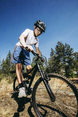 A teen boy rides his mountain bike on a trail in north Idaho. Stok Fotoğraf