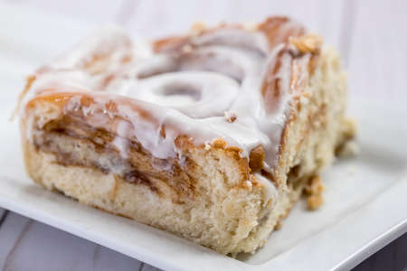 Close up of a cinnamon roll on a white plate.