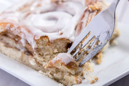 Using a fork to pick up a piece of a delicious cinnamon roll.