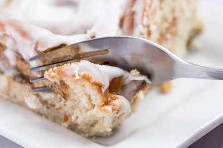 Using a fork to cut into a delicious cinnamon roll.