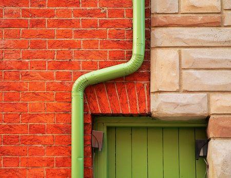 puerta verde: pared de ladrillo rojo, la lluvia cuneta en torno a las curvas de puerta verde