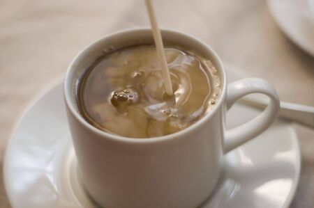 creamer: cream being poured into coffee