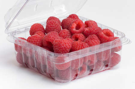 fresh, red raspberries in plastic fruit container
