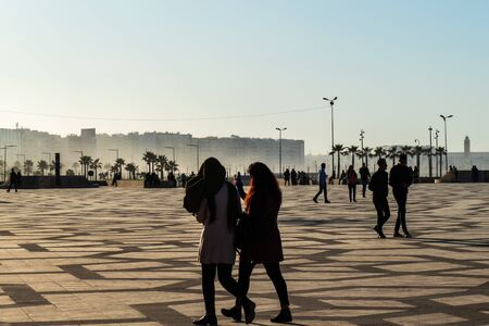 Silhouettes of young people at the square near the large mosque in Casablanca, Morocco