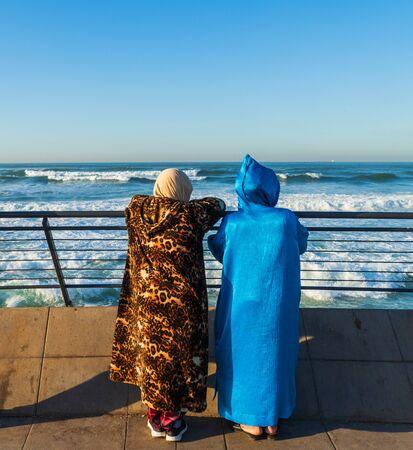 Two women watching the sea in Casablanca, Morocco Фото со стока