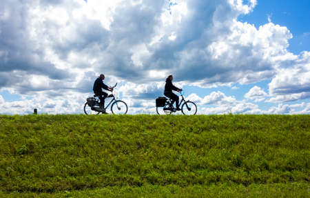 Silhouettes of cycling woman and man with a clouded sky