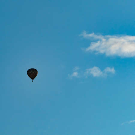 Silhouette of a hotair balloon in a blue sky with a single white cloud