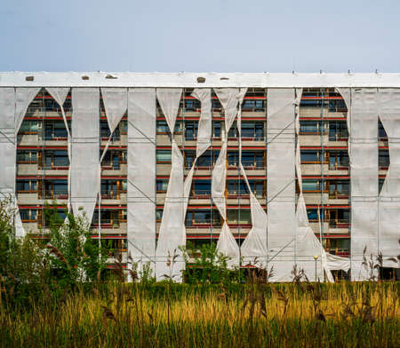 Apartment building packed in scaffoldings and covers Archivio Fotografico
