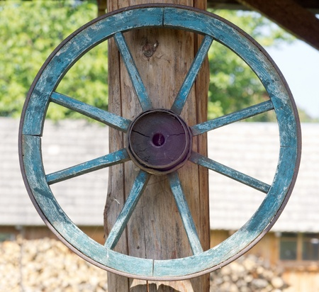 Old wooden wheel hanging on a wooden pole Stock Photo