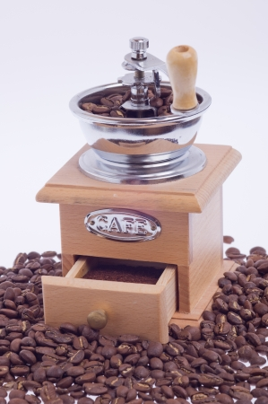 wooden coffee grinder on the coffee beans scattered Stock Photo