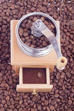 wooden coffee grinder on the coffee beans scattered Stock Photo - 15011926