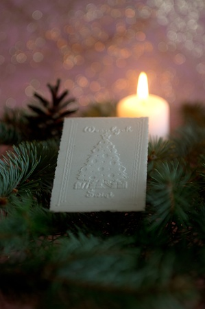 Christmas wafer on spruce branches, in  background candle