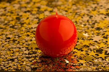 red, round candle on gold asterisks Stock Photo
