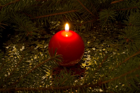 red, spherical candle, fir branches, stars