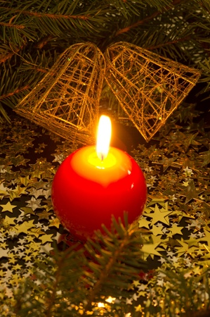 red, spherical candle and bells, fir branches, stars Stock Photo