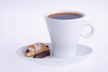 coffee with croissant and chocolate on a saucer on a white background