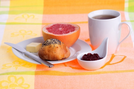breakfast with coffee, fresh bread and jam and a half of a grapefruit