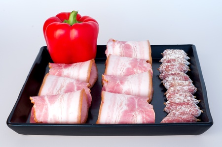 red peppers with sharp, maturing sausages and bacon, for stoneware tray photo