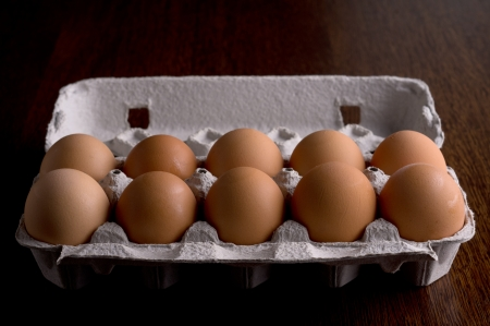 eggs in a paper on a wooden tray, dark brown table photo