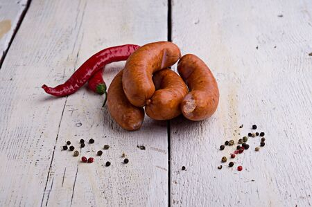 smoked sausage, peppercorns, red hot chili pepper on old wooden table Stock Photo - 18661192