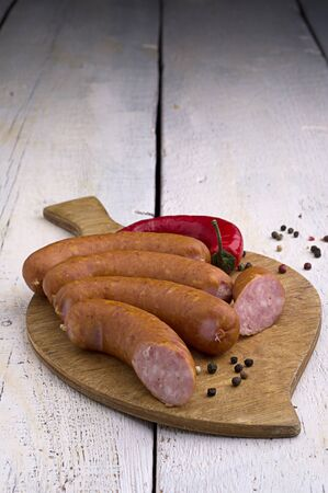 smoked sausage, peppercorns, red hot chili pepper on old wooden table Stock Photo - 18661194