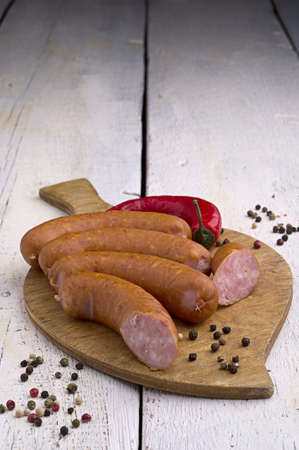 smoked sausage, peppercorns, red hot chili pepper on old wooden table Stock Photo - 18661148
