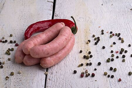 sausage, peppercorns, red hot chili pepper on old wooden table
