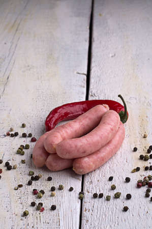 sausage, peppercorns, red hot chili pepper on old wooden table Stock Photo - 18661198