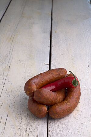 smoked sausage, peppercorns, red hot chili pepper on old wooden table Stock Photo - 18661193