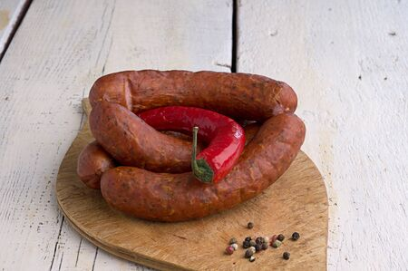 smoked sausage, peppercorns, red hot chili pepper on old wooden table Stock Photo - 18661195