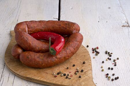 smoked sausage, peppercorns, red hot chili pepper on old wooden table