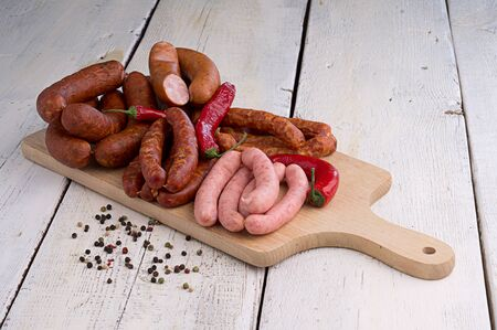 smoked sausages, peppercorns, red hot chili pepper on old wooden table Stock Photo - 18661205
