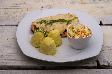 potatoes, fish baked under cheese, served with vegetable salad on old wooden table