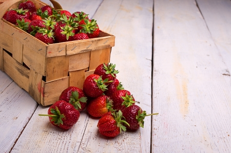 full basket of strawberries on the old, whitewashed boards