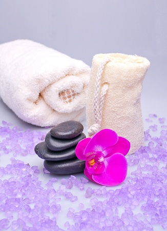 Massage stones, sponge and orchid on a white background photo