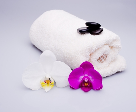 white and purple orchid, towel and massage stones