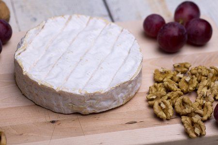 blue cheese, walnuts, grapes, on a chopping board on an old table