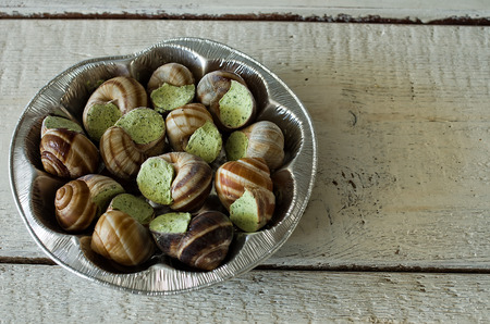 Burgundy snails on a metal tray on old table