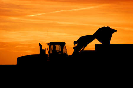 Industrial construction loader silhouette at sunrise or sunset Stock Photo
