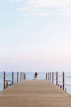 Girl sitting on the pier and looking at the sea horizon and blue sky. Vacation concept. Summer time sea vacation background