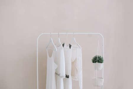 Robes blanches sur un cintre. Ensemble de robes de mariée pour femmes sur des cintres en bois, fond de mode, gros plan