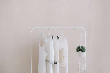 Weiße Kleider auf einem Kleiderbügel. Satz von Frauenhochzeitskleidern auf einem hölzernen Kleiderbügel, Modehintergrund, Nahaufnahme