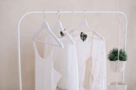 White dresses on a hanger. Set of women wedding dresses on a wooden hangers, fashion background, close up Фото со стока