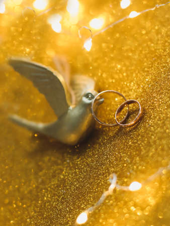 Golden wedding rings on golden background with toy bird and decorations. Shiny golden jewelry. Wedding details. Proposal of marriage, valentine gift. copy space.
