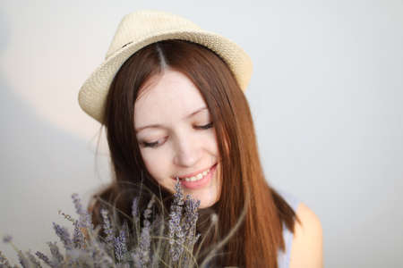 portait of a beautiful young woman wearing summer hat and holding lavender flowers