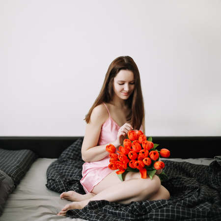 Young beautiful woman sitting in bed and holding a bouquet of red tulips Stock fotó