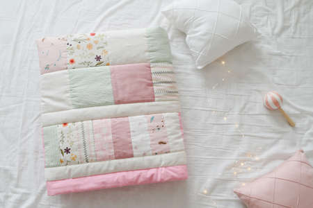 Cozy baby cot with a patchwork blanket. Baby bedding and textile for nursery Stock fotó
